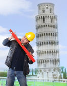 Funny picture of worried builder using a spirit level against leaning tower of Pisa. — Stock Photo