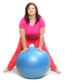 Happy overweight woman with blue ball exercising — 图库照片