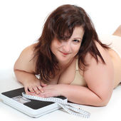 Overweight woman with a weighing machine and measure tape. — Stock Photo