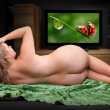 Постер, плакат: Nude woman wathing TV