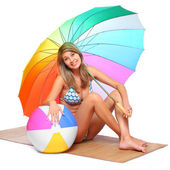 Young woman in swimsuit resting under a beach umbrella. — Stockfoto