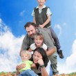 Happy family together on the grass against blue sky. — Стоковая фотография