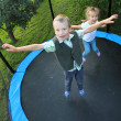 Stock Photo: Two funny kids jumping on a outdoor trampoline.
