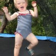 Happy girl playing on a garden trampoline. — Stock Photo