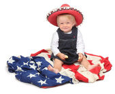 Little girl sitting in the mexican sombrero — Stock Photo