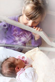 Newborn baby girl in a incubator. Her sister looking at. — Stock Photo