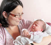 Young mother with her newborn baby. Close up with shallow DOF. — Stock Photo