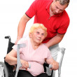 Paraplegic woman sitting in a wheelchair and her male nurse. — Stock Photo