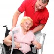 Stock Photo: Paraplegic womsitting in wheelchair and her male nurse.