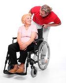 Elderly paraplegic woman sitting in a wheelchair and her male nurse — Stock Photo