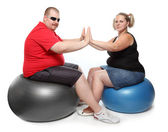 Overweight woman and man exercising sitting on blue fitness ball — Stock Photo