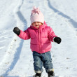 Little girl on a winter snowy road. — Stock Photo