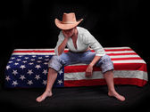 Depressed cowboy on a american flag. Economic crisis metaphor. — Stock Photo