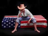 Depressed cowboy on a american flag. Economic crisis metaphor. — Stock Photo