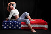 Happy american girl on a flag. Independence day concept. — Stock Photo