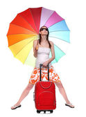 Happy young woman going on vacations with her suitcase and rainbow umbrella. — Stock Photo