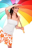 Young woman going on vacation with her rainbow umbrella. — Stock Photo