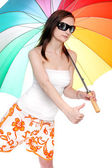 Young woman going on vacation with her rainbow umbrella. — Zdjęcie stockowe