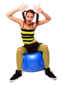 Teenage girl. doing grimace, sitting on pilates ball — Stock Photo