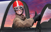 Beautiful girl in a cockpit of a vintage plane. Close up with shallow DOF. — Stock Photo