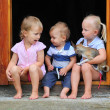 Funny kids and puppy playing in the doorway to an rural house. — Stock Photo