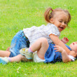 Two happy playing childs on a green grass — Stock Photo