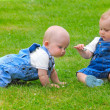 Two happy children are playing on green meadow — Stock Photo