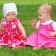 Two little sisters sitting on a grass. — Stock Photo