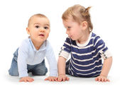 Playing children. An girl with her little brother on a white background. — Stock Photo