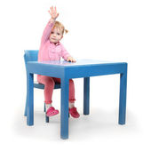 Little scholar in the school desk. — Foto de Stock