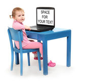 Little scholar in a school desk with laptop. — Foto de Stock