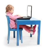 Little scholar in a school desk with laptop. — Stock fotografie