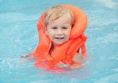 Little child in the life jacket floating — ストック写真