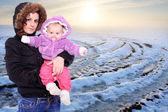 Young highlander with her baby dressed in a fur in snowy mountains. Seasonal fashion shot. — Stock Photo