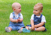 Two talking children on green meadow. — Stock Photo