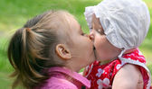 Little sisters kissing — Stockfoto