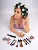 Young beautiful girl is having hair curlers on her head — Stock Photo