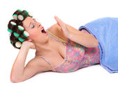 Yawning young woman with colorful hair-curlers — Stock Photo