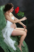 Beautiful pregnant woman with flower — Stock Photo