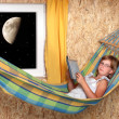 Resting young girl on a hammock in living room - nightshot — Stock Photo #33182611