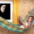 Resting young girl on a hammock in living room - nightshot — Stock Photo