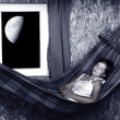 Resting young girl on a hammock in living room - nightshot — Stock Photo #33182627