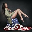 Young attractive girl dressed in old battle coat sitting on american flag. — Foto de Stock