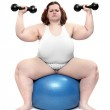 Shot of a happy overweight young woman with blue ball on a white background. — Stock Photo #33186025