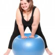 Shot of a happy overweight young woman with blue ball on a white background. — Stock Photo #33186109