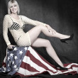 Young attractive pin up girl dressed in net lingerie sitting on american flag — Stok fotoğraf