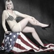 Young attractive pin up girl dressed in net lingerie sitting on american flag — Стоковая фотография