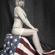 Young attractive pin up girl dressed in net lingerie sitting on american flag — Stock Photo