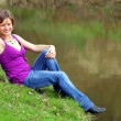 Happy young girl dresed in blue jeans siting on a river bank in first spring day. — Stock Photo