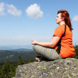 Young woman meditating on a high peak. — Stock Photo